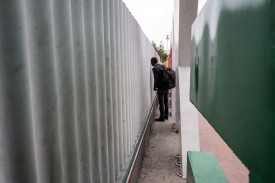 An asylum-seeker from Mauritania looks through the bars of a fence at a U.S.-Mexico border crossing in Tijuana, Mexico, on May 31.