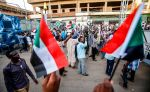 Sudanese supporters of the ruling Transitional Military Council chant slogans and wave national flags during a rally in Khartoum on May 31.
