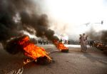 A Sudanese protester walks past burning tires as military forces tried to disperse a sit-in outside army headquarters in Khartoum, Sudan, on June 3.