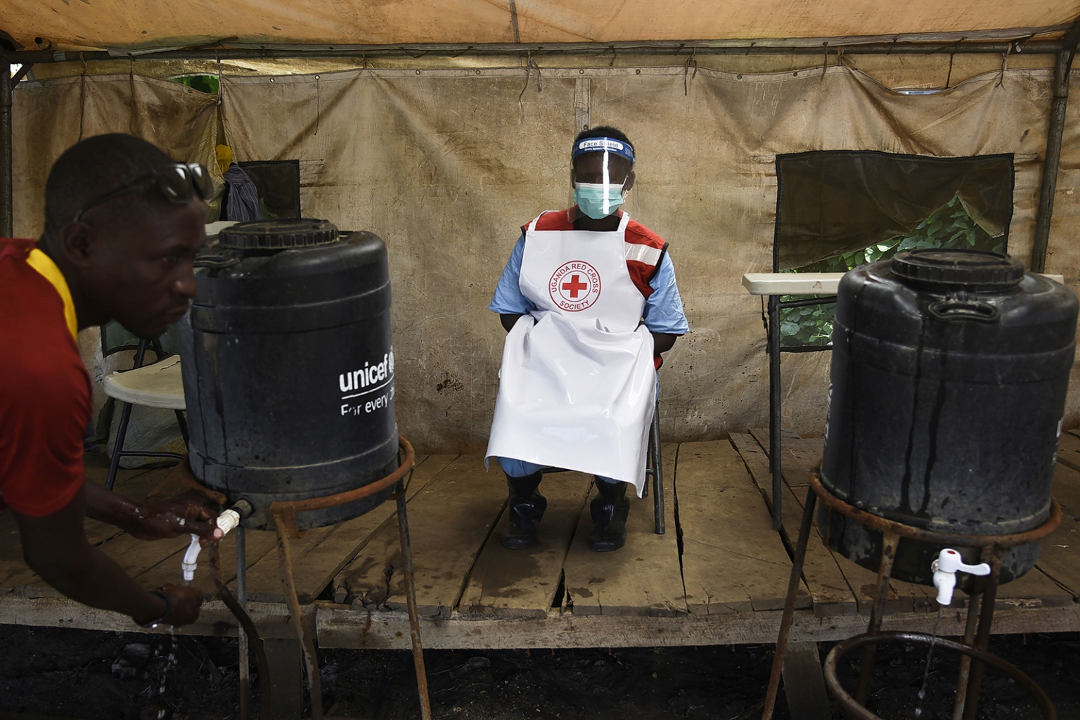 A health worker ensures that people wash their hands at the Mpondwe Health Screening Facility in the Uganda border town with Democratic Republic of the Congo on June 13. Health officials say a woman in Uganda died from Ebola, the second fatality in the country since a major outbreak in Congo crossed the border. ISAAC KASAMANI/AFP/Getty Images