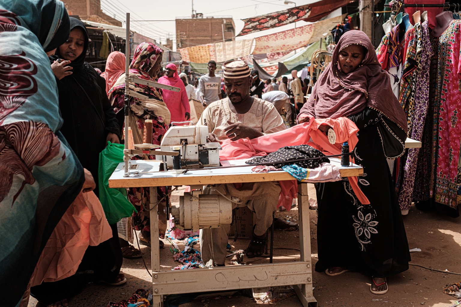 A tailor works with customers at a market street in Omdurman, the twin city of the Sudanese capital Khartoum, on June 13. YASUYOSHI CHIBA/AFP/Getty Images