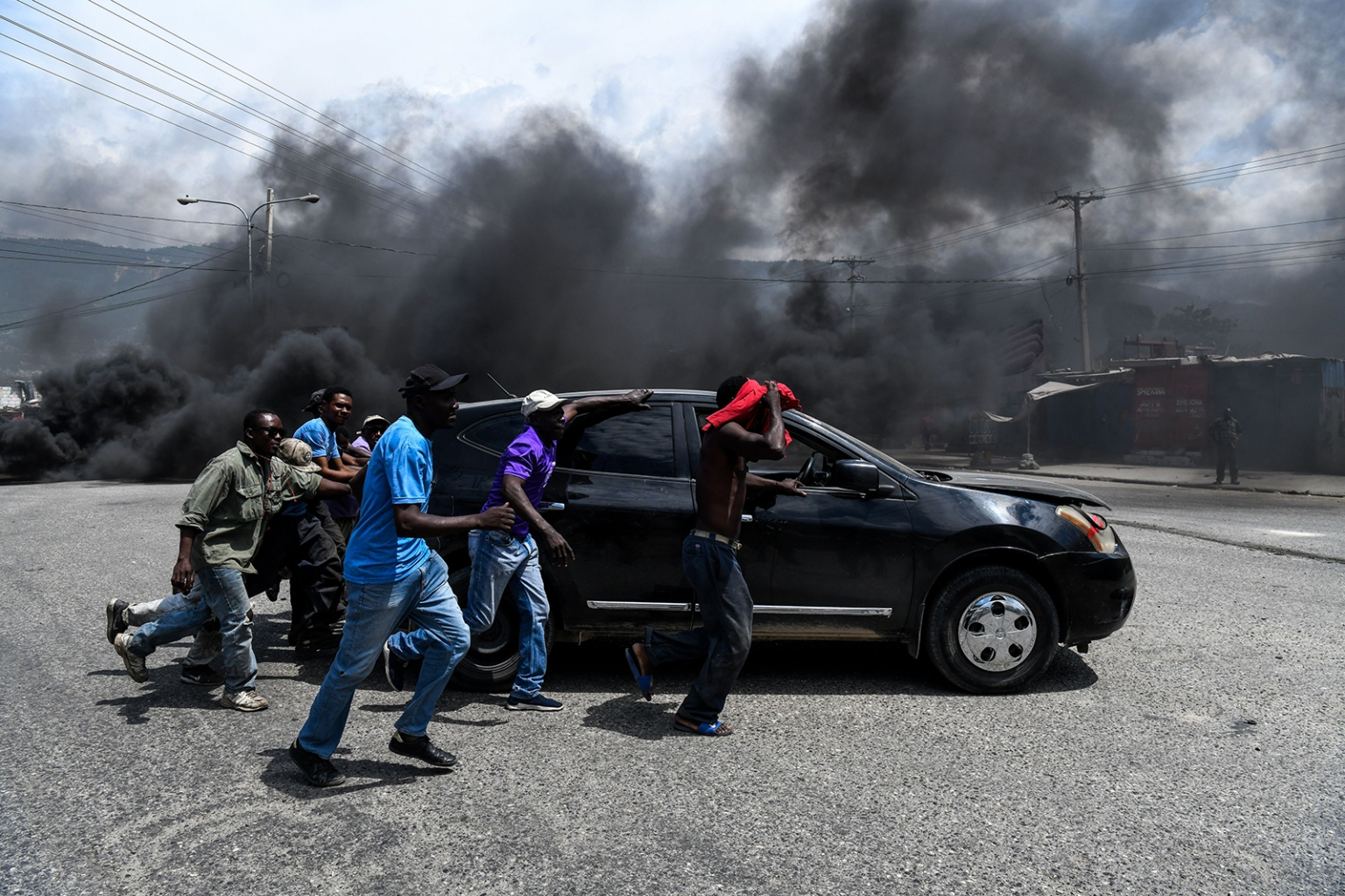 People drag a car from the street as demonstrators burn tires during a protest against the ruling government in Port-au-Prince on June 13. CHANDAN KHANNA/AFP/Getty Images