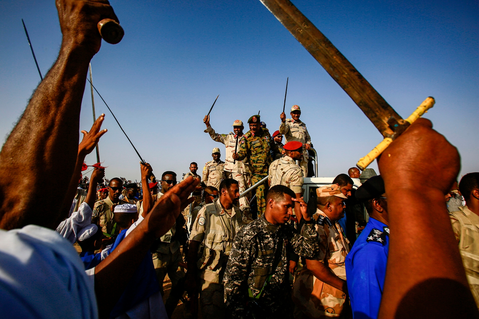 Mohamed Hamdan Dagalo, also known as Himediti, commander of the Rapid Support Forces (RSF) paramilitaries, waves a baton as he rides in the back of a vehicle surrounded by RSF members and crowds of supporters in the village of Qarri, Sudan, on June 15. ASHRAF SHAZLY/AFP/Getty Images