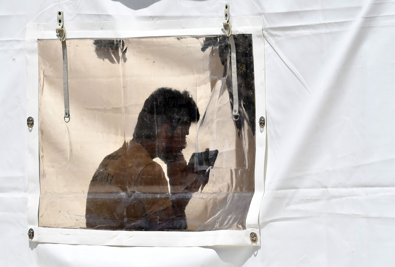 An illegal migrant attempts to contact family on his cell phone as he stands inside a tent at the Vucjak camp on the outskirts of Bihac in northern Bosnia on June 16. ELVIS BARUKCIC/AFP/Getty Images