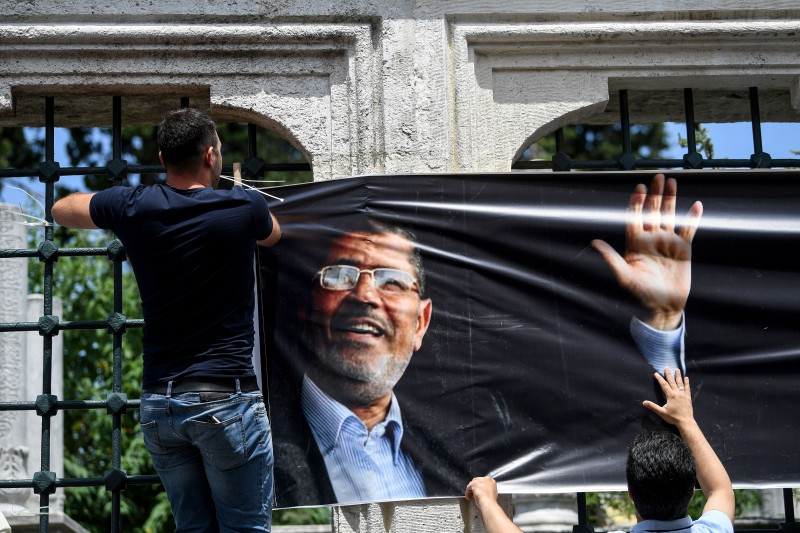 A man hangs a poster of Egyptian President Mohamed Morsi as people attend symbolic funeral cerenomy on June 18,2019 at Fatih mosque in Istanbul.