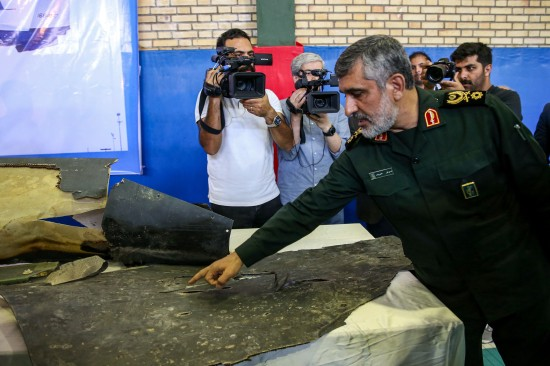 Gen. Amir Ali Hajizadeh, the head of the aerospace division of Iran's Islamic Revolutionary Guards Corps, speaks to media next to debris from a downed U.S. drone in Tehran on June 21.