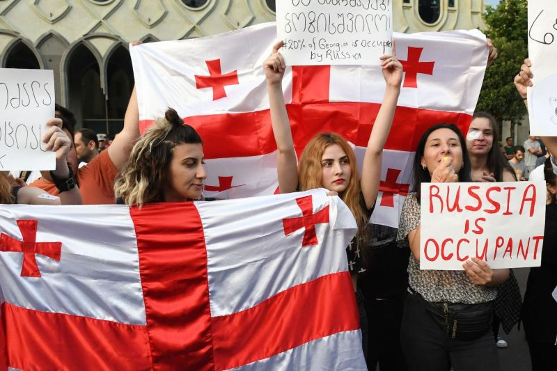Protesters hold signs Georgian flags during a rally in front of the parliament building in Tbilisi on June 21.