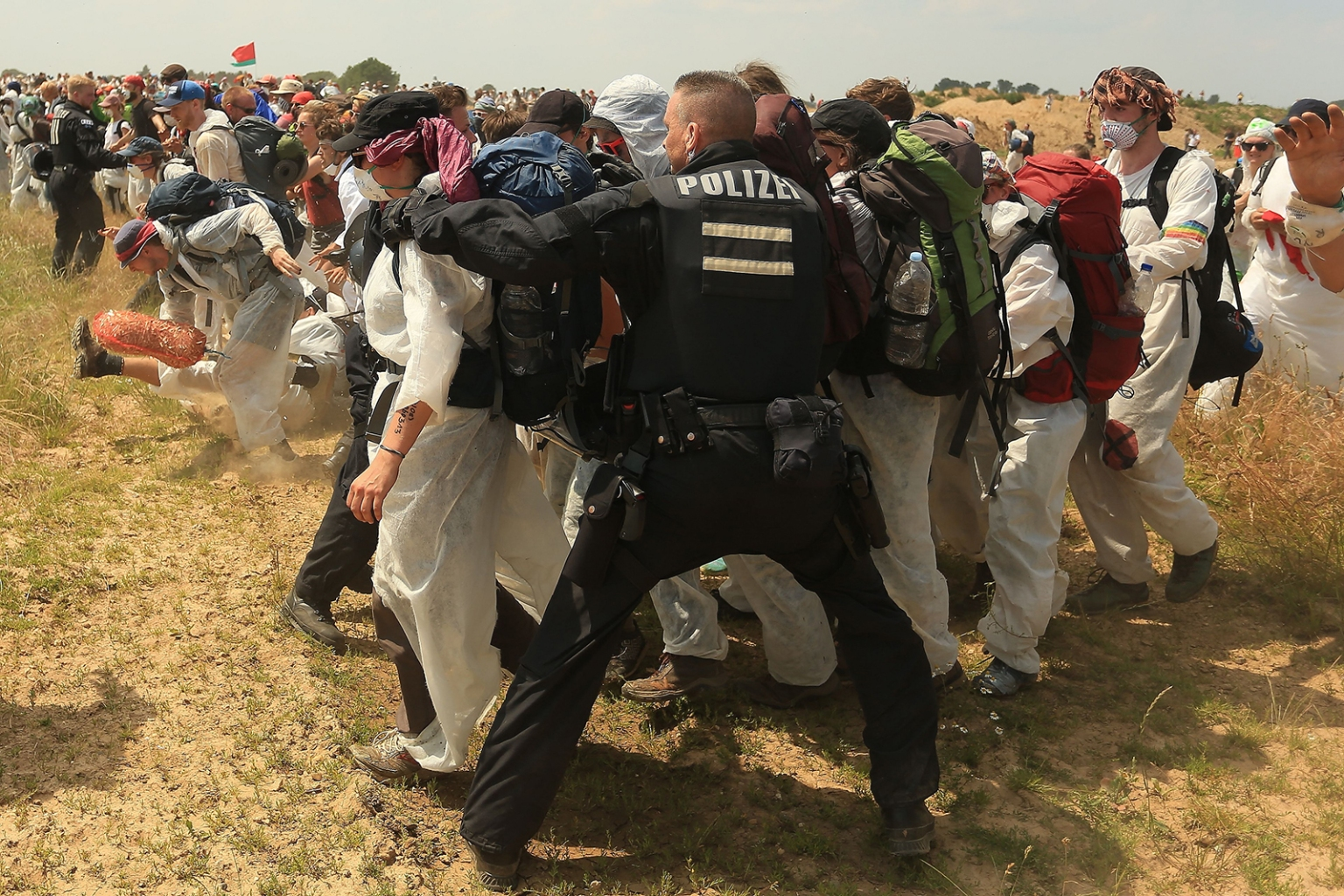 "Policemen try to prevent climate activists from entering the grounds of a coal mine in Garzweiler, western Germany, on June 22, during a weekend of massive protests in a growing ""climate civil disobedience"" movement. DAVID YOUNG/AFP/Getty Images"