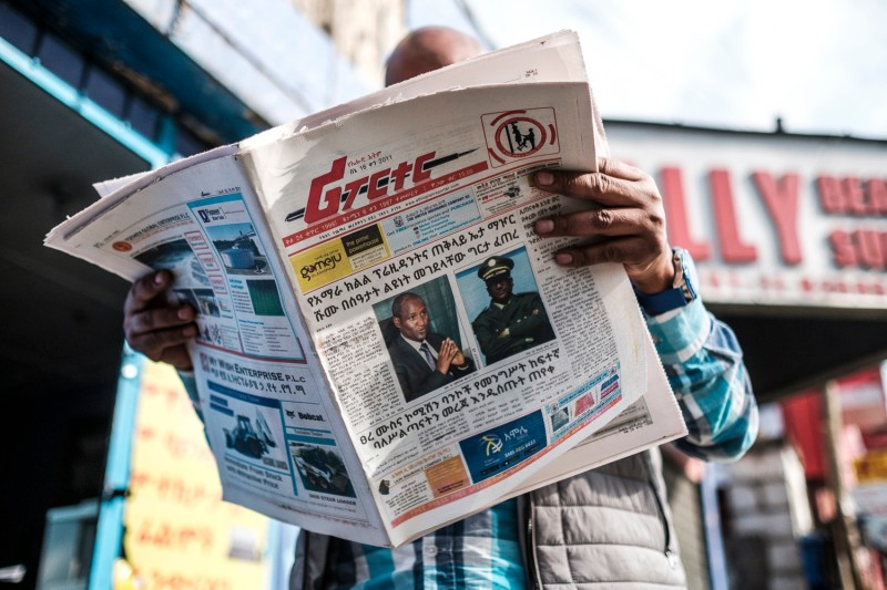 A man reads the Reporter, an Ethiopian newspaper, depicting the portraits of Ambachew Mekonnen, the president of the country's Ahmara region, and of Gen. Seare Mekonnen, the chief of staff of the Ethiopian National Defense Force, in Addis Ababa on June 24.