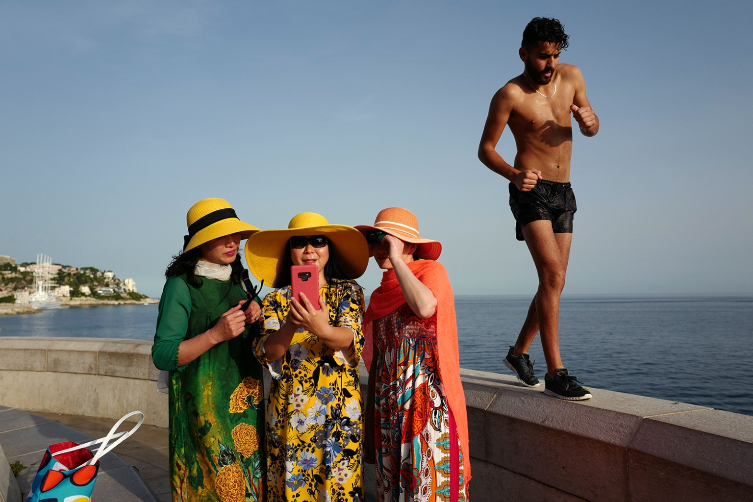 A man walks by as tourists take selfies in the French Riviera city of Nice as temperatures soar above 90 degrees Fahrenheit on June 24. VALERY HACHE/AFP/Getty Images