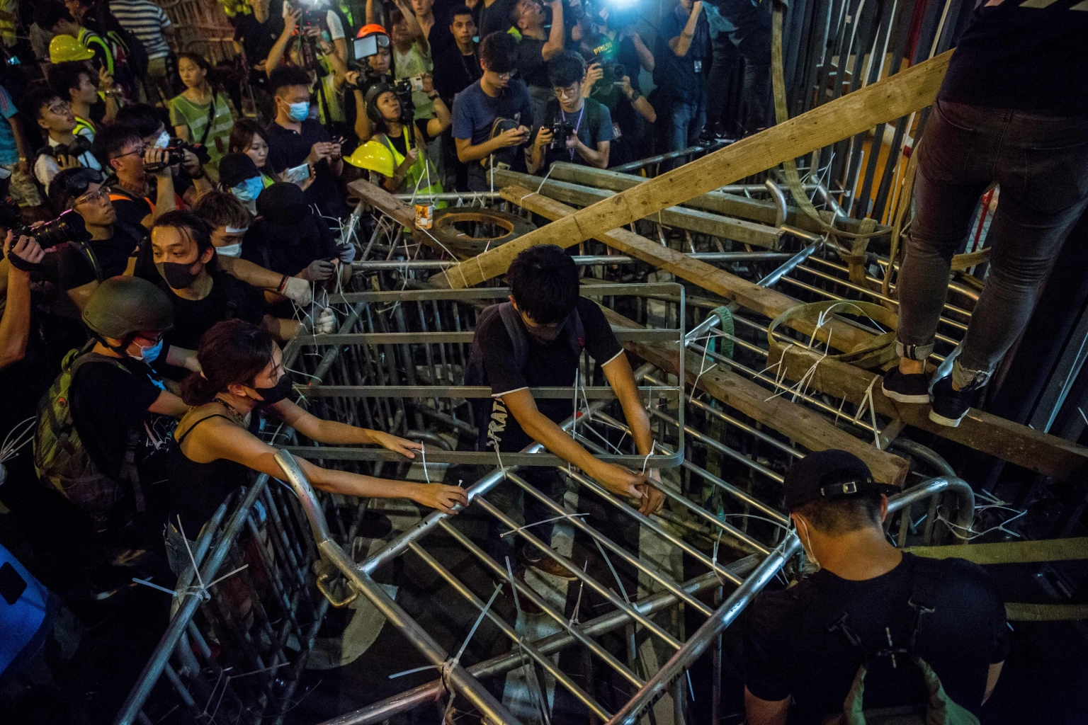 Protesters secure barricades to a gate at the police headquarters in Hong Kong late on June 26. ISAAC LAWRENCE/AFP/Getty Images