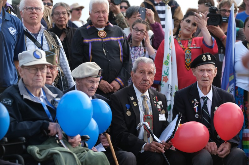 U.S. and British World War II veterans gather at the U.S. 1st Infantry Division memorial on a hill that overlooks Omaha Beach in Normandy to commemorate the World War II Allied D-Day invasion in Colleville-sur-Mer, France, on June 3.
