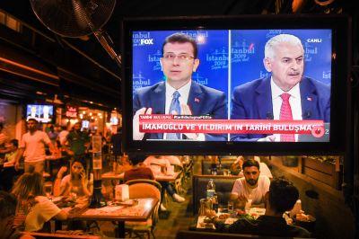 People in a restaurant watch a televised lived debate between mayoral candidates Binali Yildirim and Ekrem Imamoglu in Istanbul on June 16.