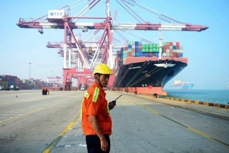 A Chinese worker looks on as a cargo ship is loaded at a port in Qingdao, China, on July 13, 2017.