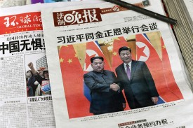 The front page of a Chinese evening newspaper, showing images of a 2018 meeting between China's President Xi Jinping with North Korean leader Kim Jong Un, is displayed in Beijing on March 28, 2018.