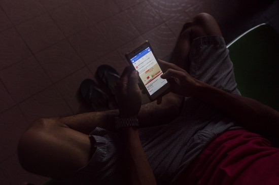 A man uses Facebook on a mobile phone in Yangon on June 7, 2018.