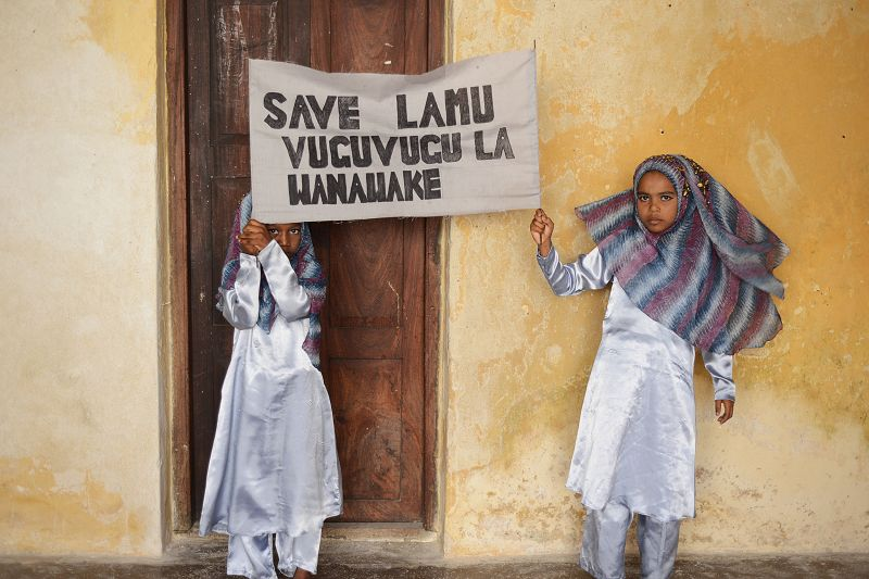 "Local students hold a sign that reads ""Save Lamu Women's Movement"" in Swahili at a poetry competition in Lamu Town to raise awareness about the effects of coal on the environment on Nov. 29, 2017."