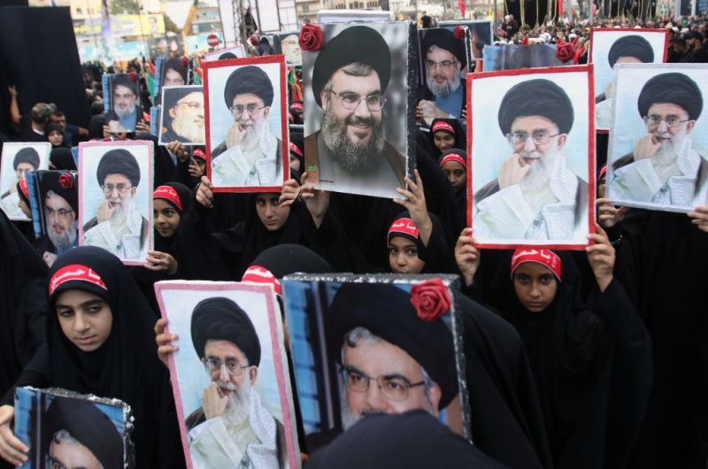 Children of members of Lebanon's Shiite Hezbollah movement hold portraits of Hezbollah chief Hasan Nasrallah and Iran's supreme leader Ayatollah Ali Khamenei during a procession following the mourning period of Ashura in the southern Lebanese city of Nabatieh on Oct. 4, 2017.