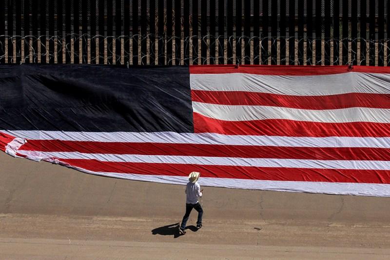 A man places a U.S. flag on the border wall between El Paso, Texas, and Ciudad Juárez, Mexico, on June 6.