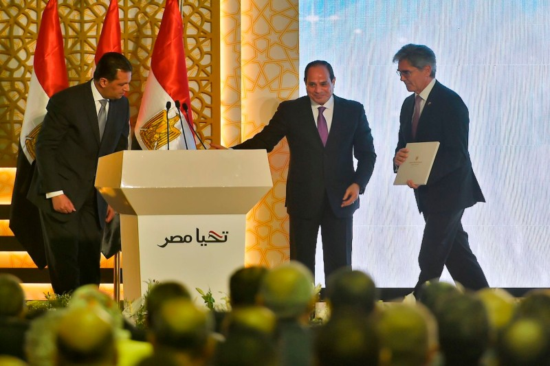 Egyptian President Abdel Fattah al-Sisi (C) welcomes Joe Kaeser (R) the CEO of German engineering giant Siemens during the inauguration of three large power plants on the outskirts of Cairo on July 24, 2018.