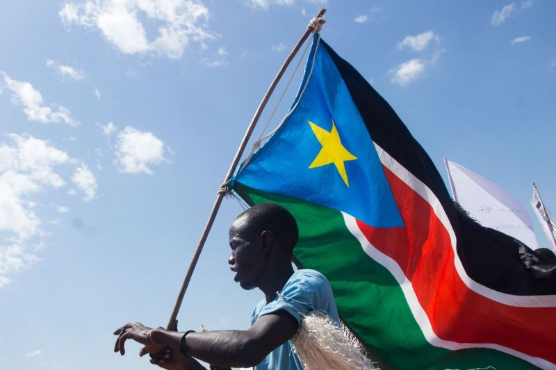 A man carries South Sudan's national flag at Mangateen Internal Displaced persons (IDPs) center during the visit of South Sudan's vice president in Juba on Nov. 17, 2018.