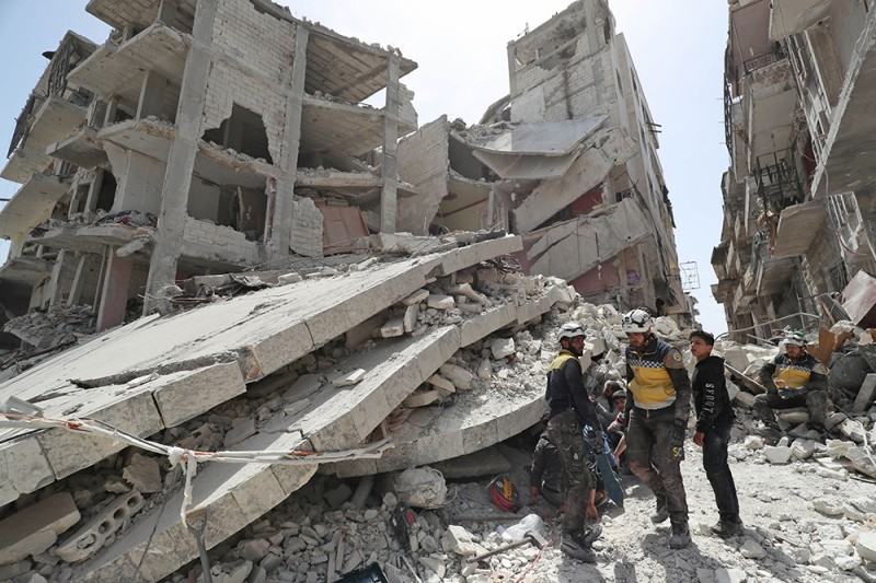 Members of the White Helmets search the rubble of a collapsed building in Jisr al-Shughur, Syria, on April 24.