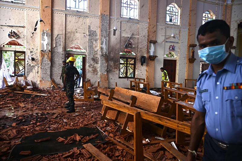 Security personnel inspect a church in Negombo, Sri Lanka, on April 22, a day after it and other locations were targeted in a series of bomb blasts.