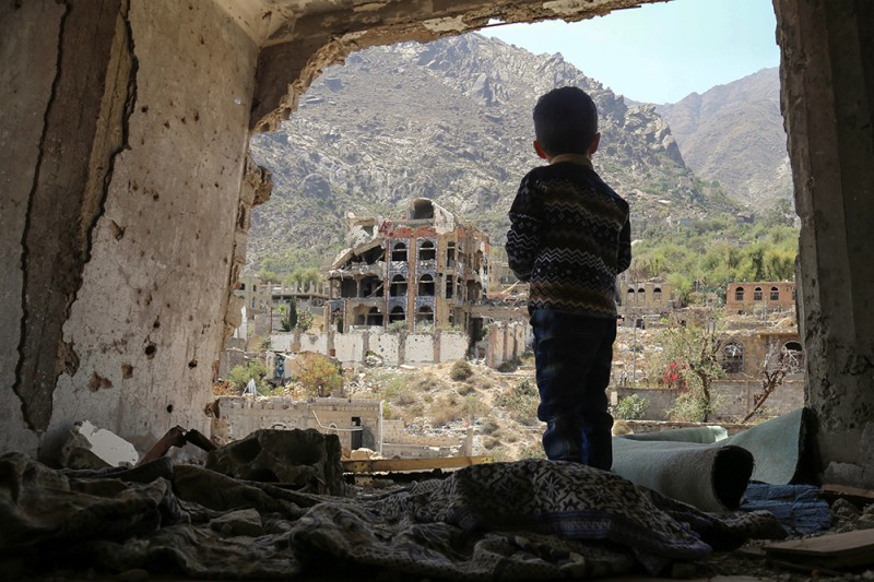 A Yemeni child looks out at buildings damaged in an airstrike in the southern Yemeni city of Taez on March 18, 2018.