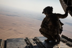 A Coalition Forces CH-47 Chinook crew member looks down from the sky during a transport mission in northeastern Syria on June 22.