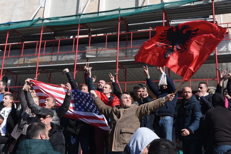 Albanian opposition supporters wave their national flag and a U.S. flag during a protest demanding the resignation of the Albanian prime minister outside the government building in Tirana on Feb. 16.