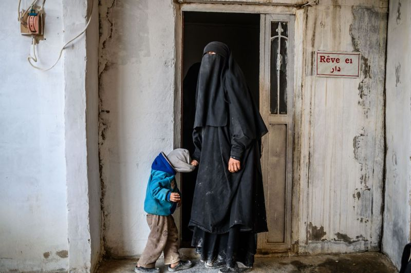 A detained French woman who fled the Islamic State walks with her child at al-Hol camp for displaced people in northeastern Syria on Feb. 17.
