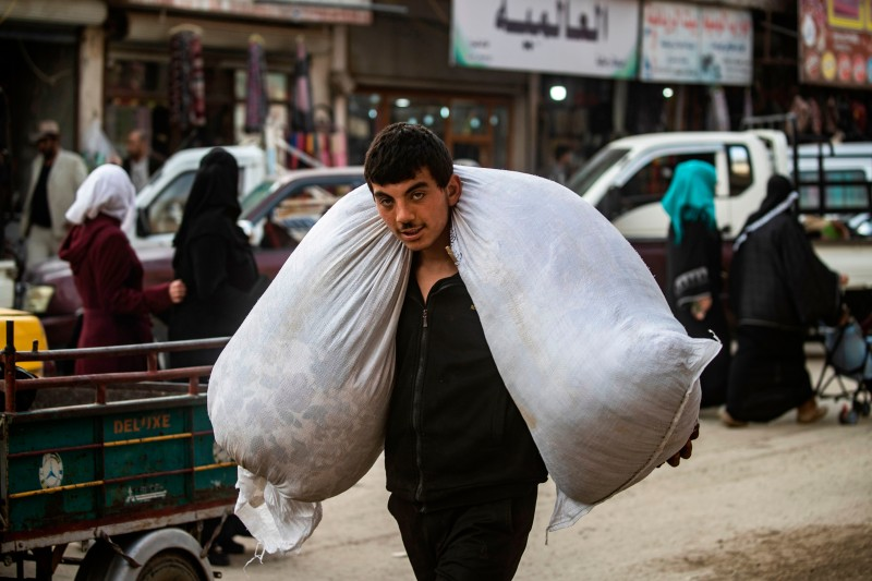 A man carries a bag across his shoulders in the northern Syrian city of Raqqa, the former Syrian capital of the Islamic State group, on May 1.
