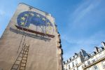 A trompe l'oeil shows two workers painting the European Union flag on the side of a building in Paris on May 23.