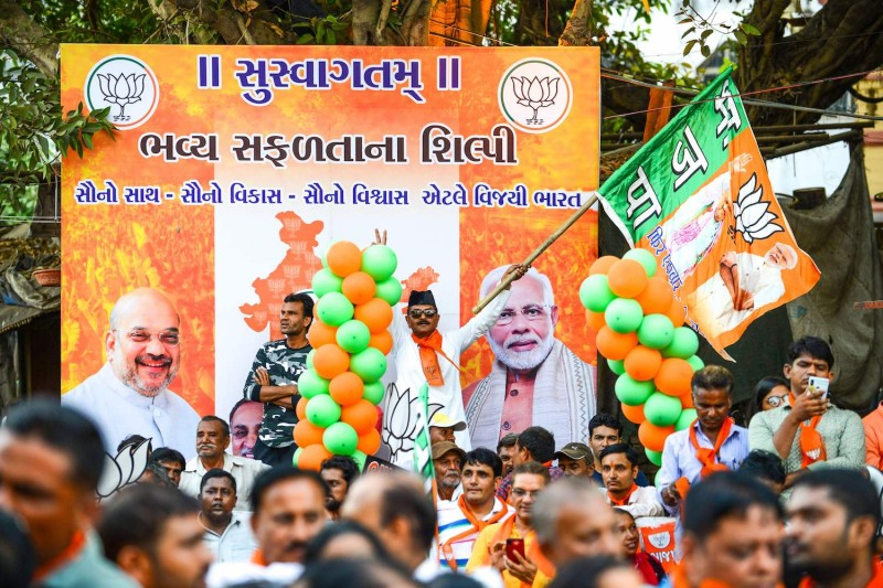 A supporter waves the Bharatiya Janata Party (BJP) flag as he participates in a rally for Indian Prime Minister Narendra Modi and BJP National President Amit Shah in Ahmedabad, on May 26.