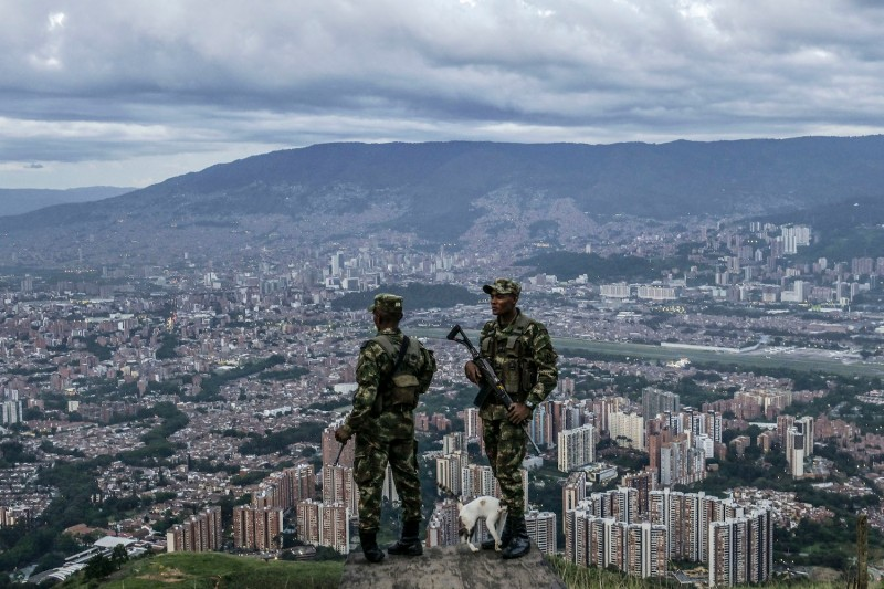 Colombian soldiers stand guard as they patrol the outskirts of Medellin, Antioquia department, on June 6.