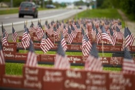 Cars pass by a memorial to American soldiers from New York state who were killed in Iraq or Afghanistan, near Canandaigua, New York, on June 4.