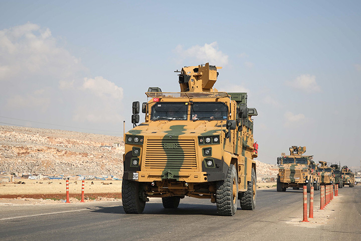 A convoy of Turkish armoured vehicles drive towards a crossing point between Syria and Turkey on a highway in the northern countryside of the Syrian province of Idlib on June 20.
