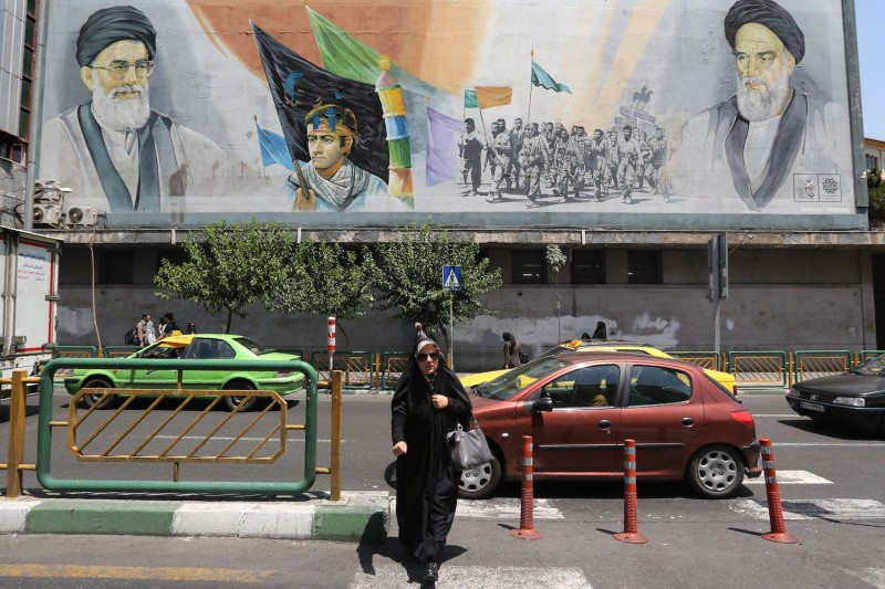 An Iranian woman walks past a mural painting depicting the late founder of the Islamic Revolution Ayatollah Ruhollah Khomeini and Iran's supreme leader Ayatollah Ali Khamenei in the Iranian capital Tehran on June 25, 2019.