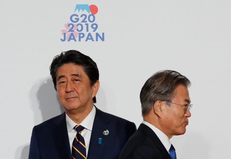 South Korean President Moon Jae-In is welcomed by Japanese Prime Minister Shinzo Abe before a family photo session at the G-20 summit in Osaka, Japan, on June 28.