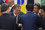 South Korea's President Moon Jae-in and Japan's Prime Minister Shinzo Abe shake hands at the G20 Summit in Osaka on June 29.