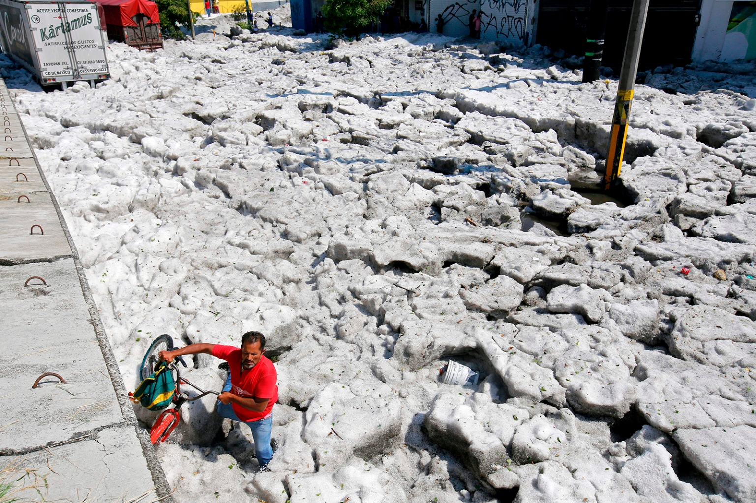 A man with a bike walks on hail in Guadalajara, Mexico, on June 30. The accumulation of hail in the streets buried vehicles and damaged homes. ULISES RUIZ/AFP/Getty Images