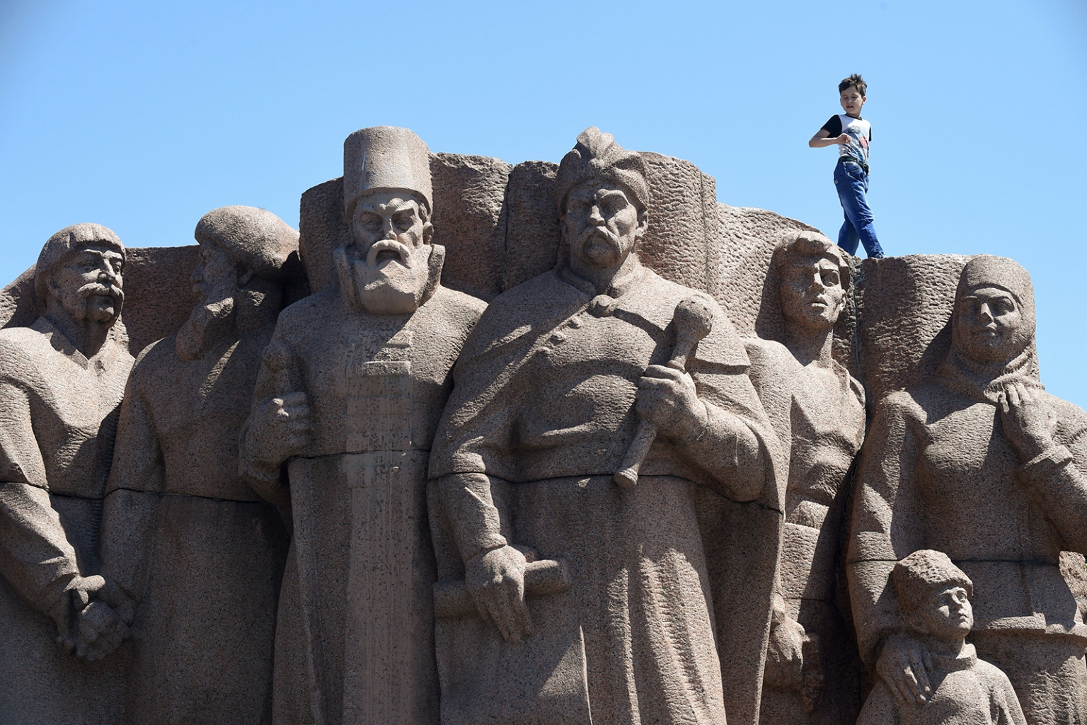 A boy walks on the top of a Soviet-era monument for Ukraine and Russia union in Kiev on July 1. SERGEI SUPINSKY/AFP/Getty Images