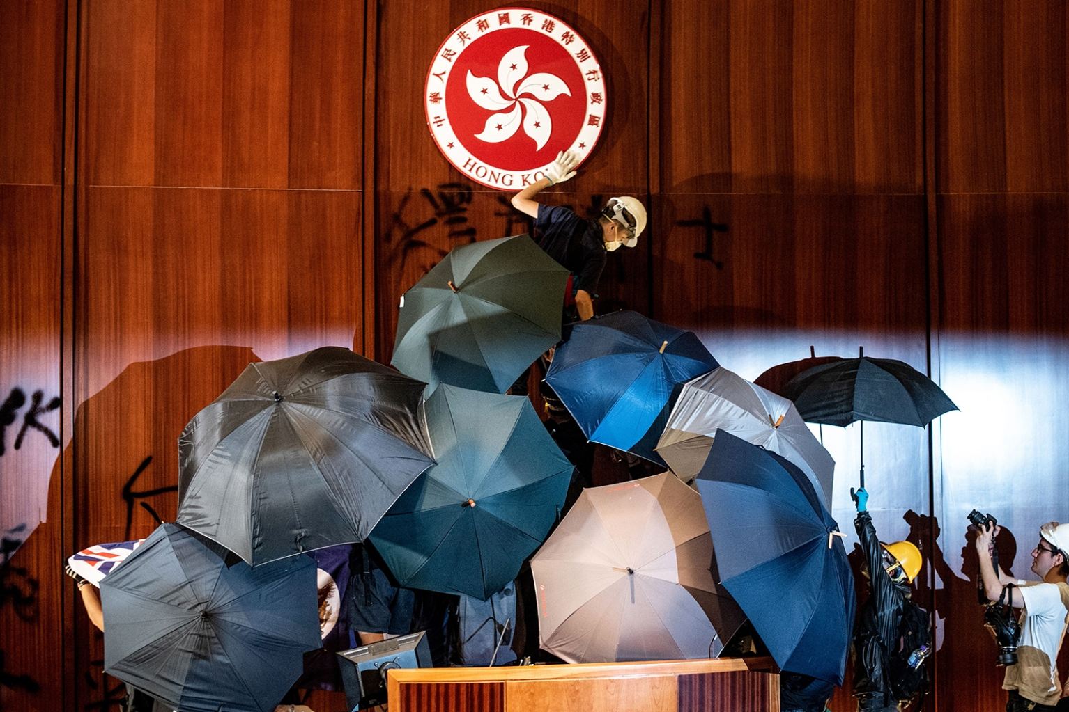 A protester defaces the Hong Kong emblem after protesters broke into the government headquarters in Hong Kong on July 1.  PHILIP FONG/AFP/Getty Images