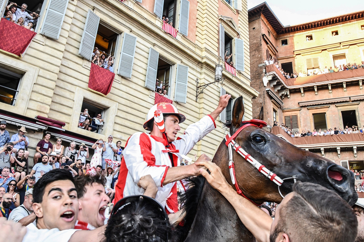 Jockey Giovanni Atzeni celebrates after winning the Palio di Siena horse race in Siena, Italy, on July 2. The Palio di Siena is held twice each year with 10 horses and riders, who ride bareback dressed in the appropriate colors representing 10 of the 17 contrade, or city wards. CARLO BRESSAN/AFP/Getty Images