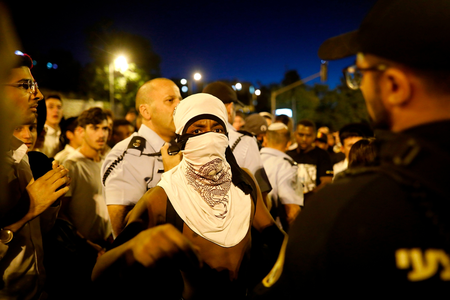 A masked member of the Israeli Ethiopian community gestures in front of policemen as demonstrators block the main entrance to Jerusalem on July 2 to protest the death of Solomon Tekah, a young man of Ethiopian origin who was killed by an off-duty police officer. MENAHEM KAHANA/AFP/Getty Images