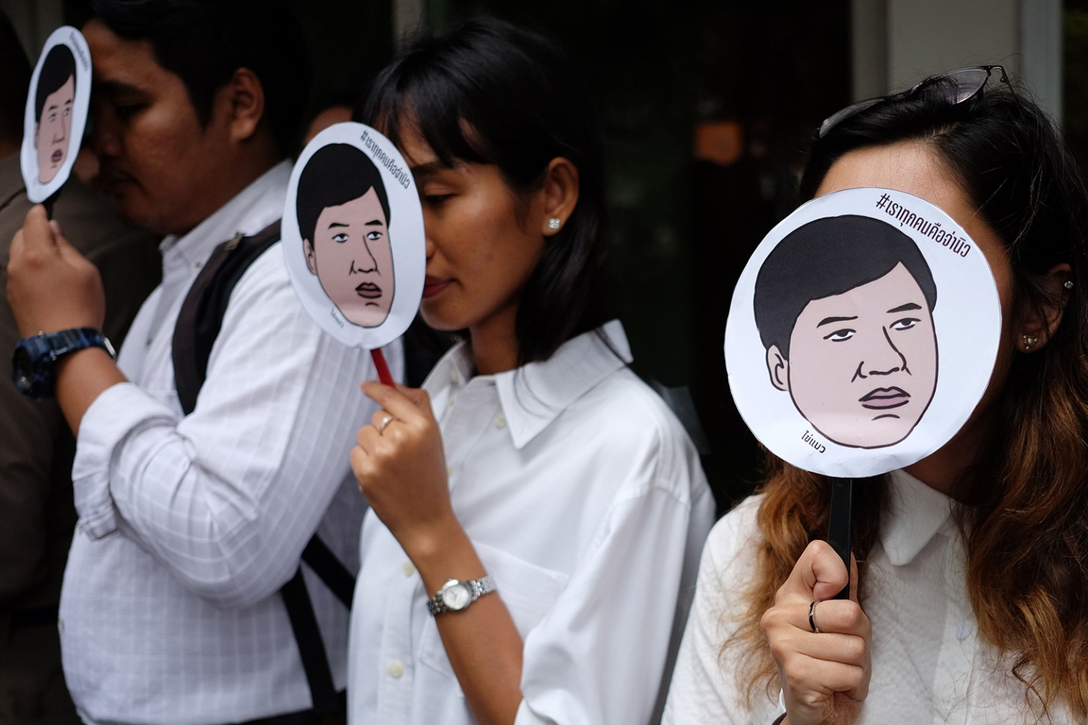 """Members of Amnesty International hold up images of Sirawith """"Ja New"""" Seritiwat, a Thai pro-democracy campaigner who was attacked by unknown assailants, during a protest in Bangkok on July 3. CANDIDA NG/AFP/Getty Images"""