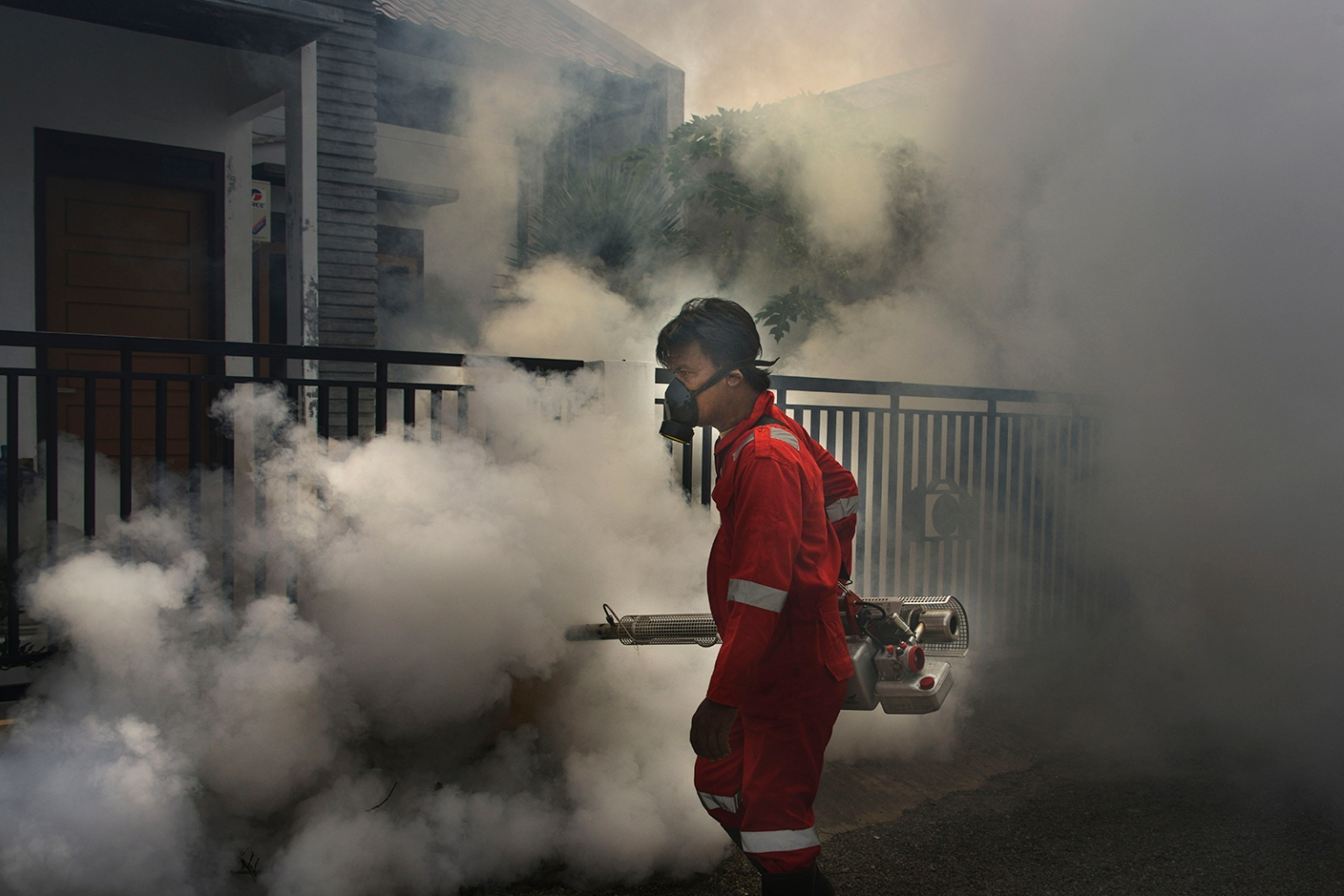 An Indonesian worker conducts mosquito fogging to minimize dengue fever cases in Banda Aceh on July 3. CHAIDEER MAHYUDDIN/AFP/Getty Images