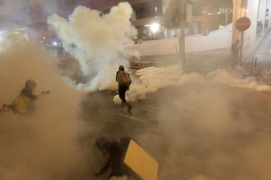 Protesters run from tear gas fired by police after a march against a controversial extradition bill in Hong Kong on July 21.  VIVEK PRAKASH/AFP/Getty Images