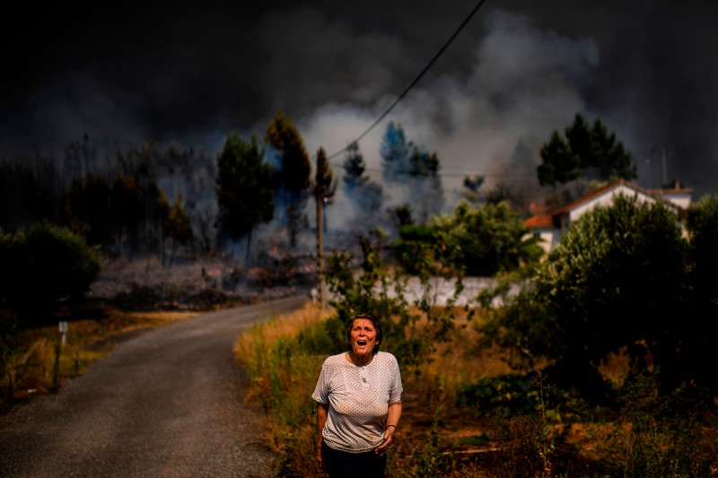 A villager shouts for help as a wildfire approaches a house at Casas da Ribeira village in Macao, central Portugal on July 21. PATRICIA DE MELO MOREIRA/AFP/Getty Images
