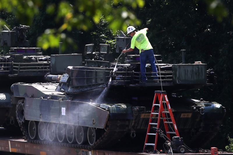 A worker washes one of two M1A1 Abrams tanks that are loaded on rail cars at a rail yard in Washington on July 2.